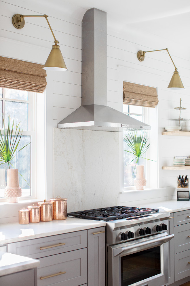Kitchen - coastal u-shaped medium tone wood floor and brown floor kitchen idea in Charleston with a farmhouse sink, shaker cabinets, gray cabinets, white backsplash, stainless steel appliances, an island and white countertops