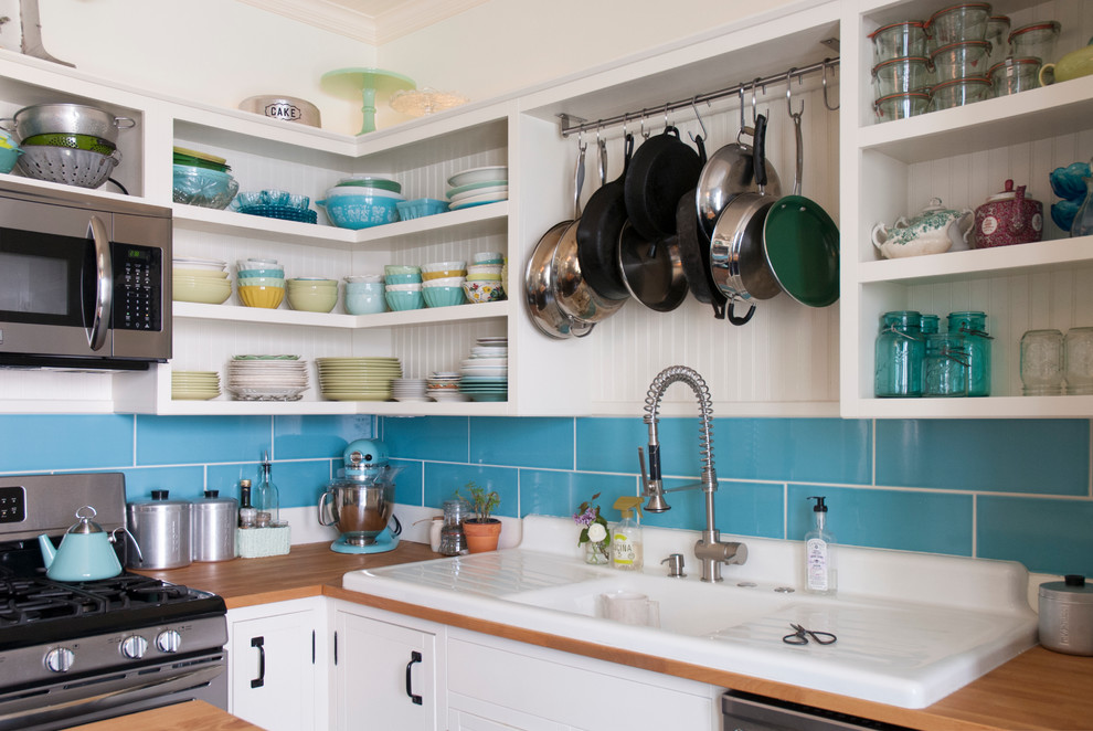 Eat-in kitchen - mid-sized eclectic l-shaped eat-in kitchen idea in Columbus with a drop-in sink, open cabinets, white cabinets, wood countertops, blue backsplash, subway tile backsplash, stainless steel appliances and an island