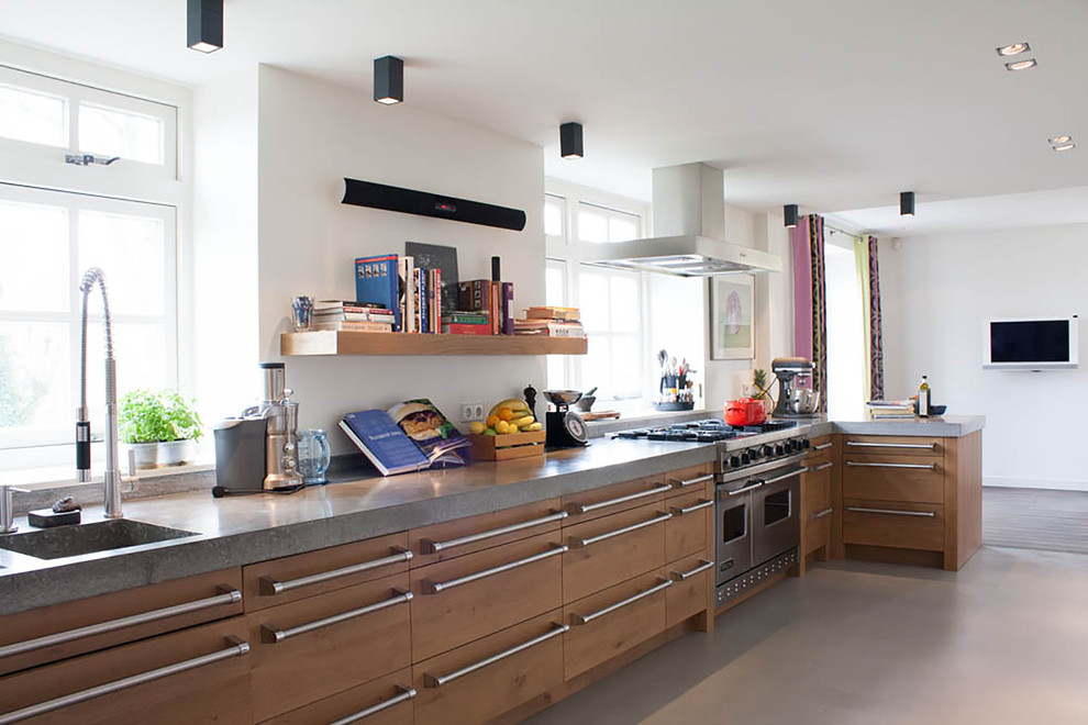 Inspiration for a contemporary kitchen remodel in Amsterdam with an integrated sink, flat-panel cabinets, light wood cabinets and stainless steel appliances