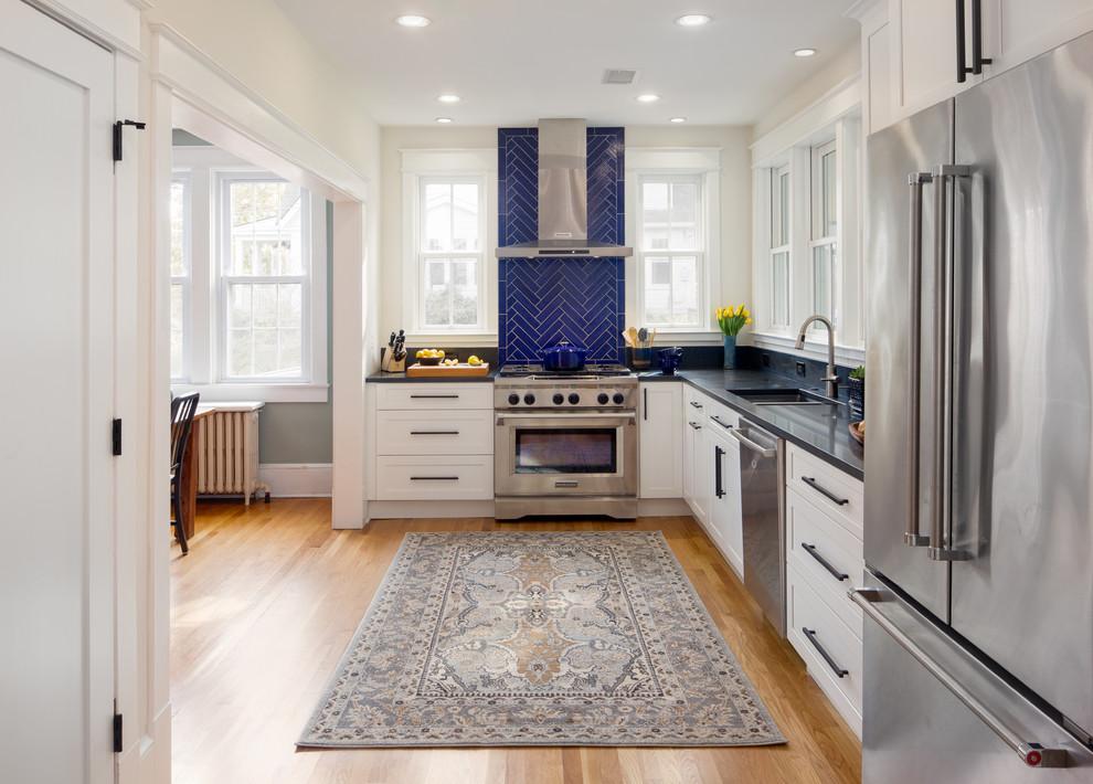 Große Klassische Wohnküche ohne Insel in L-Form mit Schrankfronten im Shaker-Stil, weißen Schränken, Granit-Arbeitsplatte, Küchenrückwand in Blau, Küchengeräten aus Edelstahl, schwarzer Arbeitsplatte, Unterbauwaschbecken, Rückwand aus Keramikfliesen, braunem Holzboden und braunem Boden in Washington, D.C.