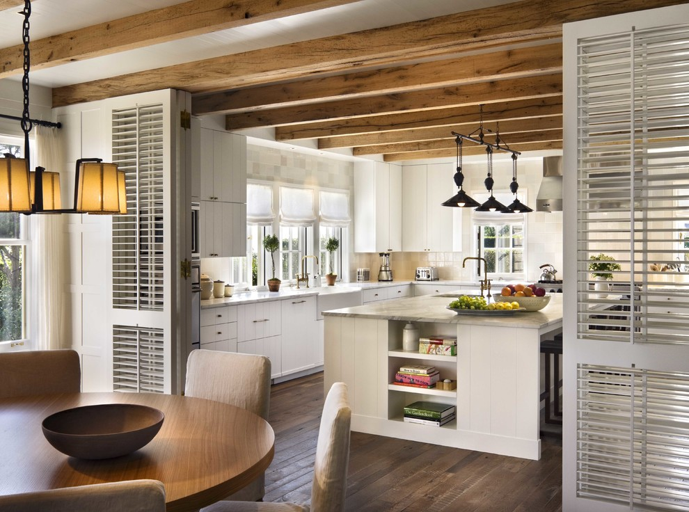 Inspiration for a mid-sized coastal l-shaped dark wood floor enclosed kitchen remodel in Boston with an island, a farmhouse sink, white cabinets, flat-panel cabinets, marble countertops, white backsplash, ceramic backsplash and stainless steel appliances