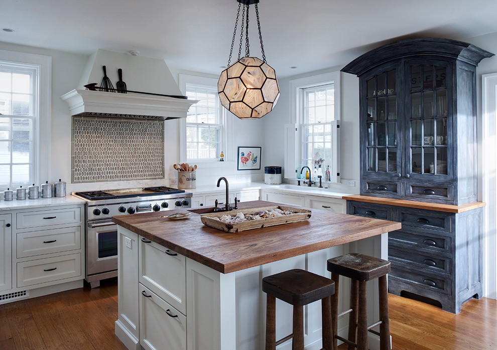 Inspiration for a transitional l-shaped kitchen remodel in Chicago with an undermount sink, recessed-panel cabinets, white cabinets, wood countertops and subway tile backsplash