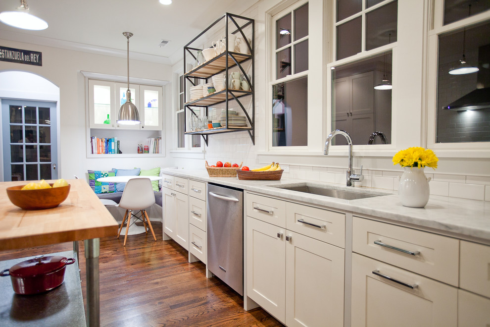 Large trendy galley medium tone wood floor kitchen photo in New York with an undermount sink, shaker cabinets, white cabinets, white backsplash, stainless steel appliances, marble countertops and an island