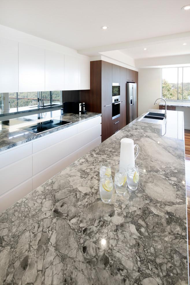 Imagen de cocina comedor contemporánea con encimera de mármol, salpicadero metalizado, salpicadero con efecto espejo, suelo de madera en tonos medios y una isla