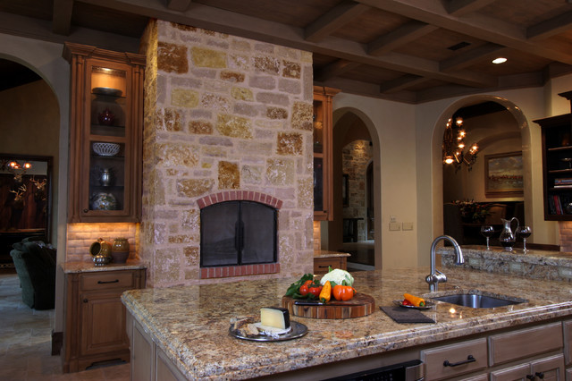 Natural tuscan inspired kitchen view of fireplace for Mediterranean fireplace designs