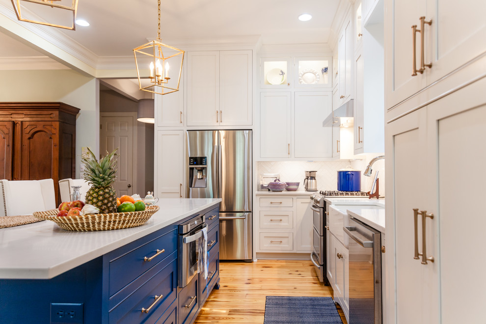 Open concept kitchen - large transitional l-shaped medium tone wood floor open concept kitchen idea in Charleston with a farmhouse sink, beaded inset cabinets, blue cabinets, quartz countertops, white backsplash, subway tile backsplash, stainless steel appliances and an island