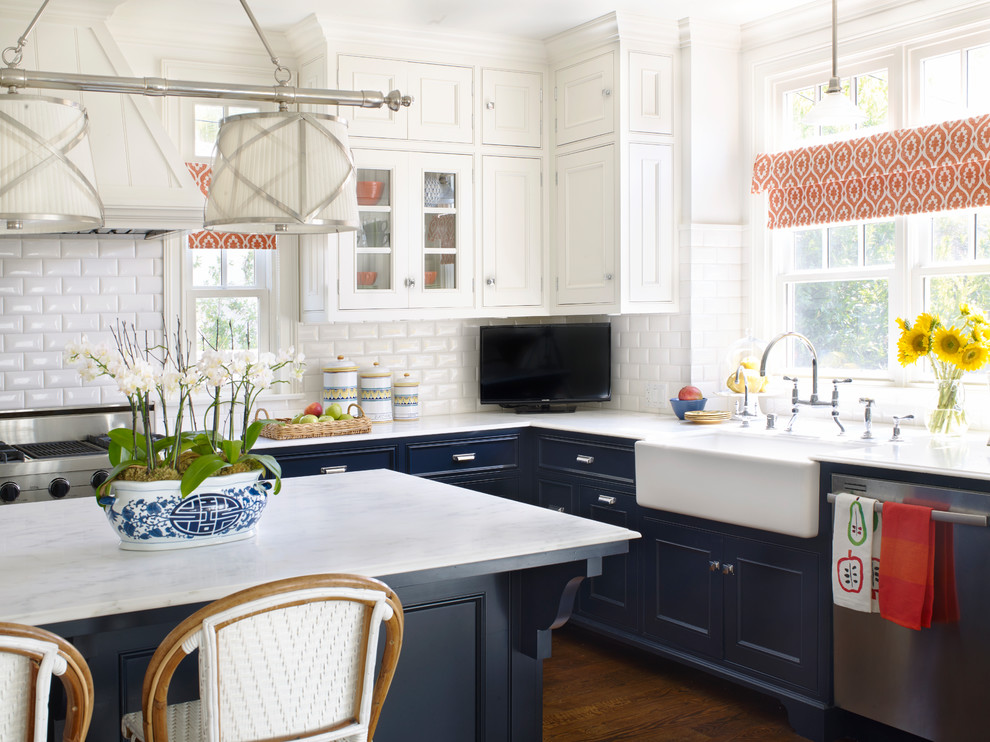 Eat-in kitchen - large traditional eat-in kitchen idea in Los Angeles with a farmhouse sink, raised-panel cabinets, blue cabinets, marble countertops, white backsplash, ceramic backsplash, stainless steel appliances and an island