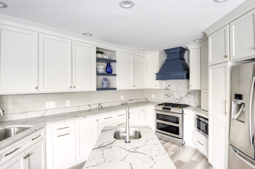 Inspiration for a mid-sized transitional u-shaped laminate floor and gray floor open concept kitchen remodel in DC Metro with an undermount sink, shaker cabinets, white cabinets, quartzite countertops, stainless steel appliances, an island and white countertops