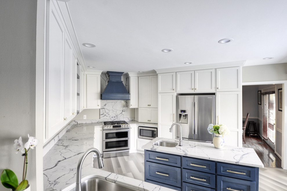 Mid-sized transitional u-shaped laminate floor and gray floor open concept kitchen photo in DC Metro with an undermount sink, shaker cabinets, white cabinets, quartzite countertops, stainless steel appliances, an island and white countertops