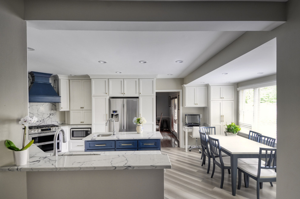 Example of a mid-sized transitional u-shaped laminate floor and gray floor open concept kitchen design in DC Metro with an undermount sink, shaker cabinets, white cabinets, quartzite countertops, stainless steel appliances, an island and white countertops