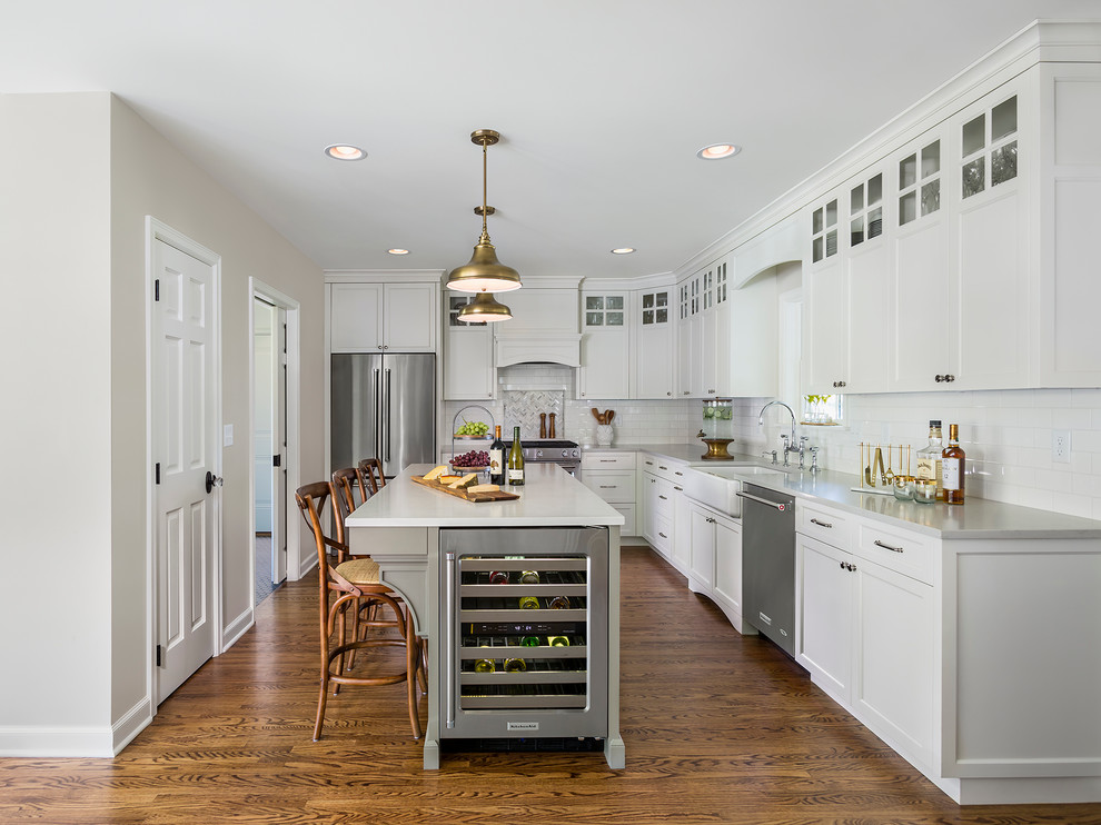 Inspiration for a mid-sized timeless l-shaped dark wood floor eat-in kitchen remodel in Minneapolis with a farmhouse sink, white cabinets, white backsplash, subway tile backsplash, stainless steel appliances, an island, shaker cabinets and quartzite countertops