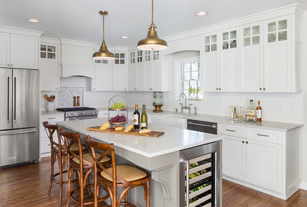 Eat-in kitchen - mid-sized transitional l-shaped medium tone wood floor eat-in kitchen idea in Minneapolis with a farmhouse sink, white cabinets, white backsplash, subway tile backsplash, stainless steel appliances, an island, shaker cabinets and quartzite countertops