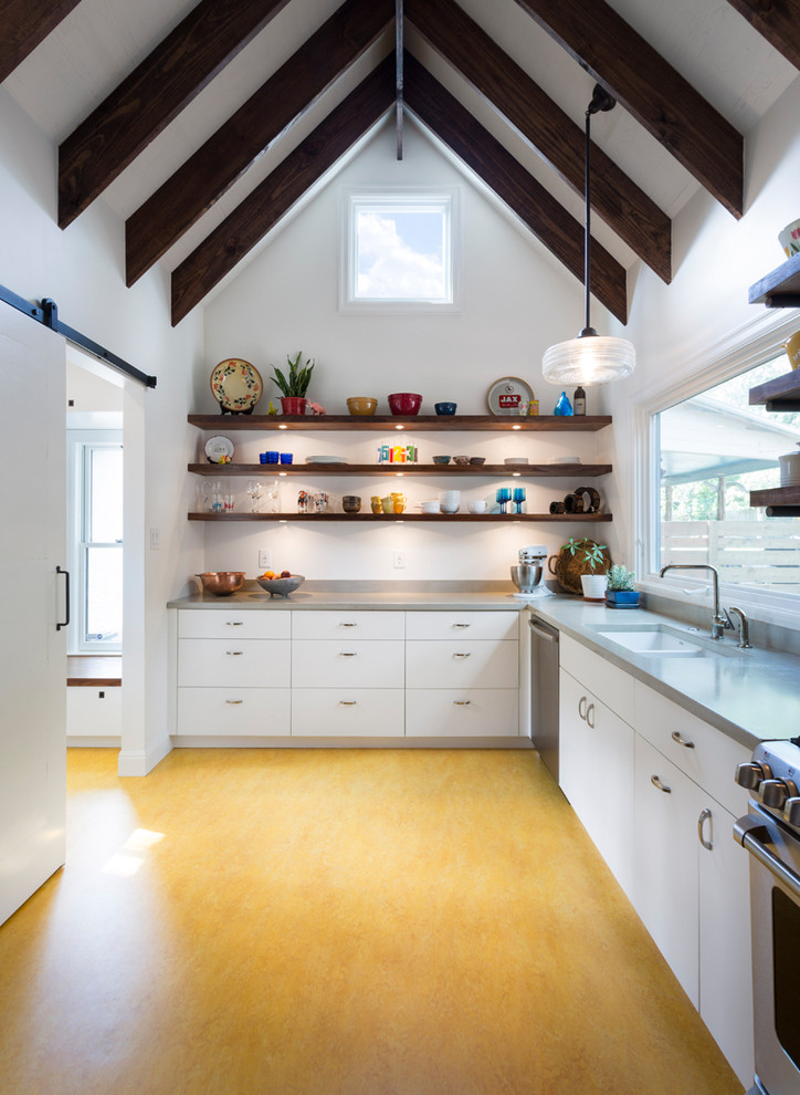 Country yellow floor kitchen photo in Austin with an undermount sink, flat-panel cabinets, white cabinets, stainless steel appliances and no island