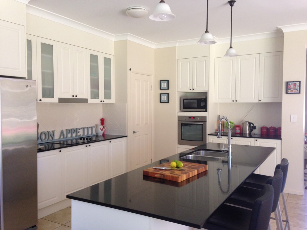 Inspiration for a large transitional l-shaped eat-in kitchen in Brisbane with an undermount sink, white cabinets, quartz benchtops, white splashback, ceramic splashback, stainless steel appliances, porcelain floors and an island.
