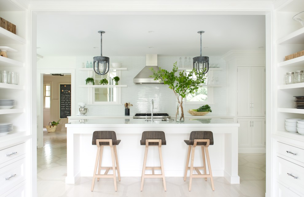 Danish kitchen photo in New York with recessed-panel cabinets, white cabinets, white backsplash, stainless steel appliances and an island