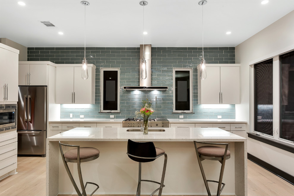 Example of a trendy kitchen design in Austin with an undermount sink, flat-panel cabinets, white cabinets, gray backsplash, subway tile backsplash, stainless steel appliances and an island