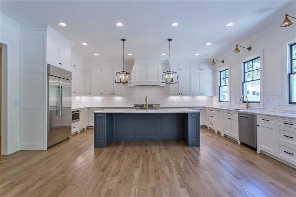 Eat-in kitchen - large transitional galley light wood floor and gray floor eat-in kitchen idea in Atlanta with a single-bowl sink, recessed-panel cabinets, gray cabinets, quartzite countertops, white backsplash, ceramic backsplash, stainless steel appliances, an island and gray countertops