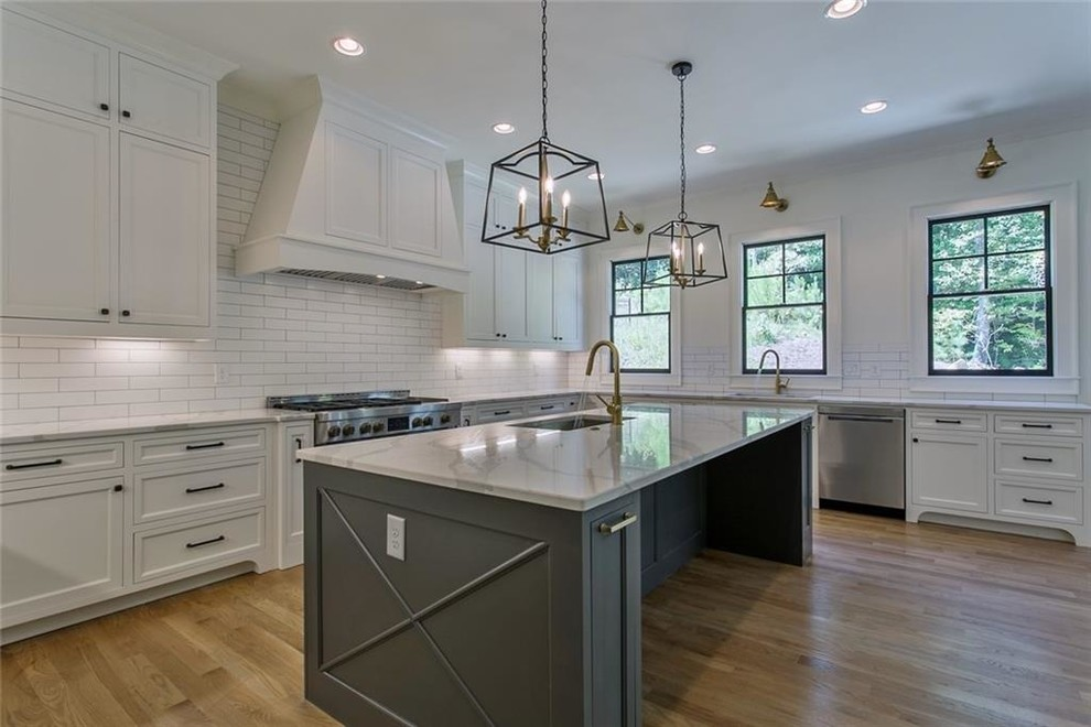 Inspiration for a large transitional galley light wood floor and gray floor eat-in kitchen remodel in Atlanta with a single-bowl sink, recessed-panel cabinets, gray cabinets, quartzite countertops, white backsplash, ceramic backsplash, stainless steel appliances, an island and gray countertops