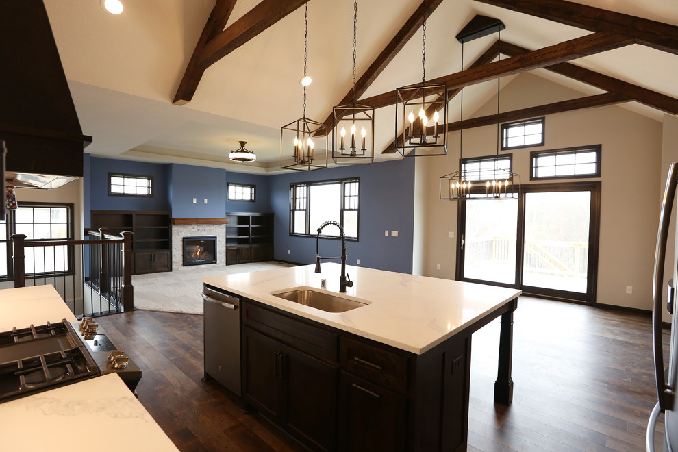 Example of a large arts and crafts l-shaped vinyl floor and brown floor open concept kitchen design in Minneapolis with an undermount sink, shaker cabinets, white cabinets, quartz countertops, white backsplash, subway tile backsplash, stainless steel appliances, an island and white countertops