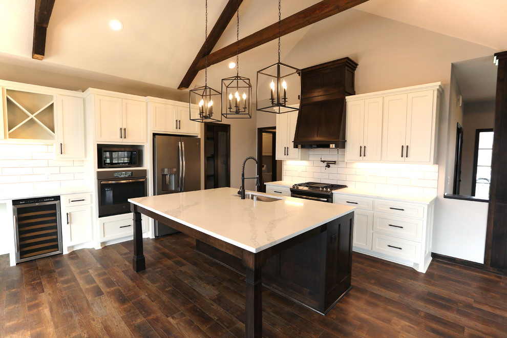 Large arts and crafts l-shaped vinyl floor and brown floor open concept kitchen photo in Minneapolis with an undermount sink, shaker cabinets, white cabinets, quartz countertops, white backsplash, subway tile backsplash, stainless steel appliances, an island and white countertops