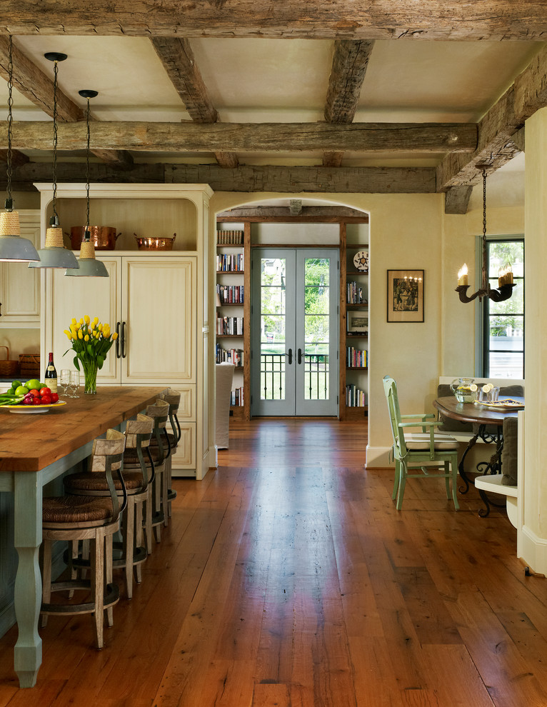Eat-in kitchen - rustic dark wood floor and brown floor eat-in kitchen idea in DC Metro with wood countertops, paneled appliances, beige cabinets, recessed-panel cabinets and an island