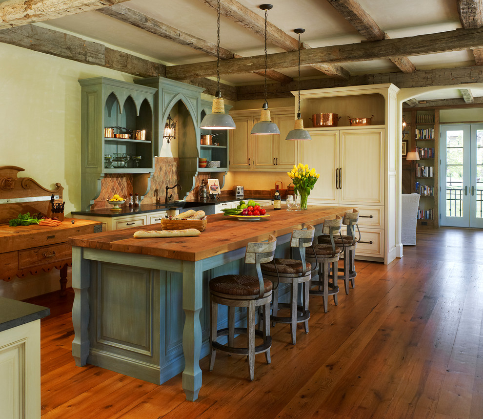 Inspiration for a mediterranean dark wood floor eat-in kitchen remodel in DC Metro with a farmhouse sink, recessed-panel cabinets, distressed cabinets, wood countertops, paneled appliances and an island