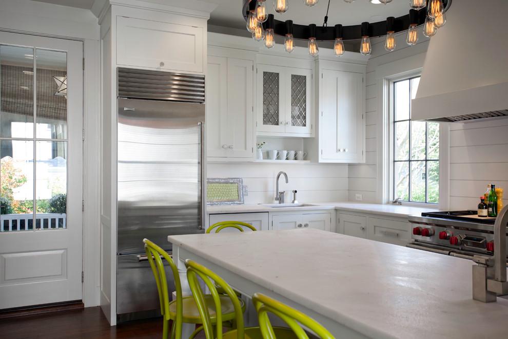 Foto de cocina clásica renovada con fregadero bajoencimera, armarios estilo shaker, puertas de armario blancas, salpicadero blanco y electrodomésticos de acero inoxidable