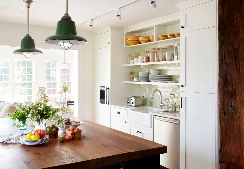Example of a classic kitchen design in New York with a farmhouse sink, wood countertops, open cabinets, white cabinets and subway tile backsplash