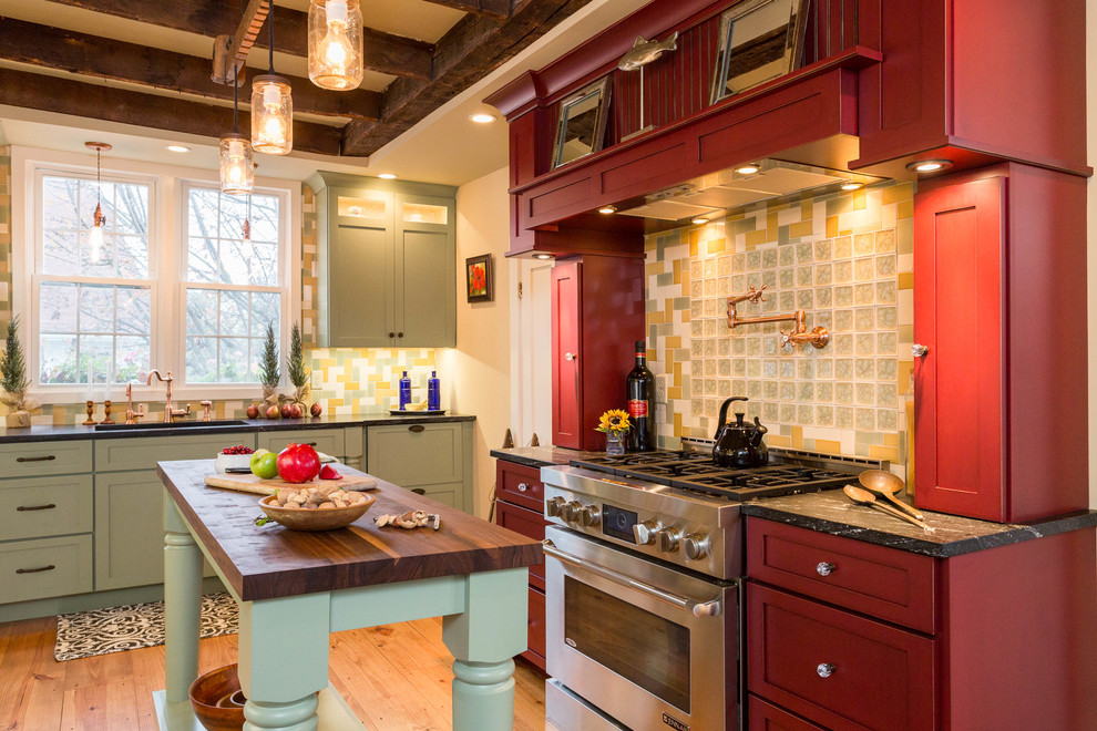 Kitchen - large cottage medium tone wood floor kitchen idea in Boston with shaker cabinets, multicolored backsplash, glass tile backsplash, an island, red cabinets, wood countertops and stainless steel appliances