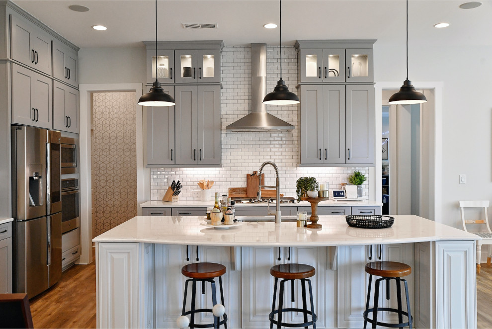 Example of a transitional l-shaped medium tone wood floor and brown floor kitchen design in Charlotte with an undermount sink, shaker cabinets, gray cabinets, white backsplash, subway tile backsplash, stainless steel appliances, an island and white countertops