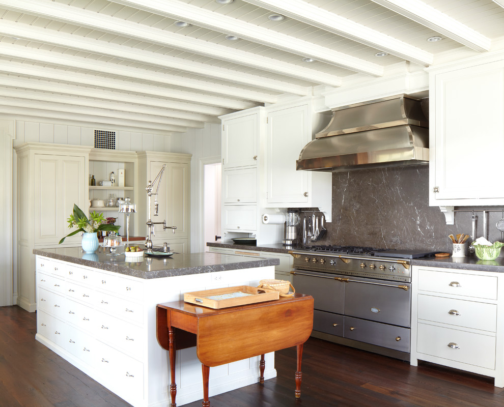 Example of a large classic single-wall dark wood floor and brown floor enclosed kitchen design in New York with marble countertops, a farmhouse sink, recessed-panel cabinets, white cabinets, gray backsplash, stone slab backsplash, stainless steel appliances and an island