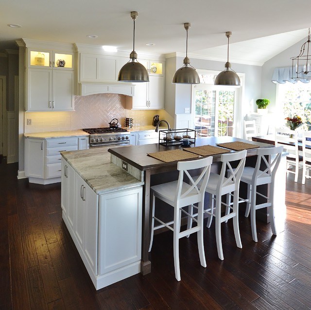 Huge transitional l-shaped dark wood floor and brown floor eat-in kitchen photo in Philadelphia with an undermount sink, raised-panel cabinets, white cabinets, granite countertops, white backsplash, subway tile backsplash, paneled appliances and an island