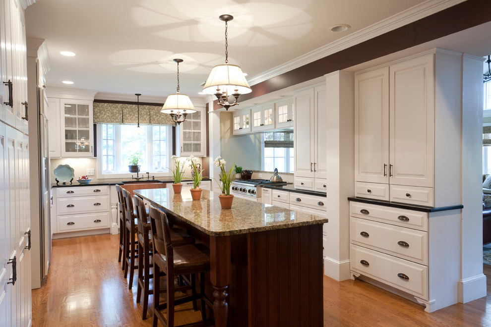 Eat-in kitchen - large traditional u-shaped medium tone wood floor and brown floor eat-in kitchen idea in Salt Lake City with an undermount sink, raised-panel cabinets, white cabinets, granite countertops, beige backsplash, paneled appliances, an island, beige countertops and ceramic backsplash