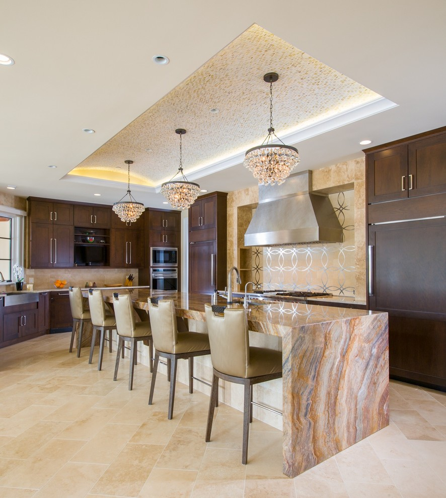 Example of a trendy l-shaped beige floor kitchen design in DC Metro with a farmhouse sink, shaker cabinets, dark wood cabinets, beige backsplash, paneled appliances and an island