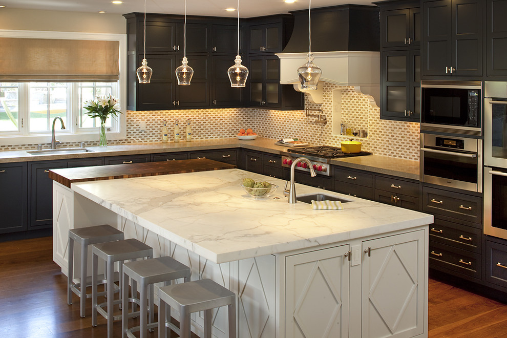 Elegant kitchen photo in San Francisco with stainless steel appliances, recessed-panel cabinets, dark wood cabinets, marble countertops and limestone backsplash