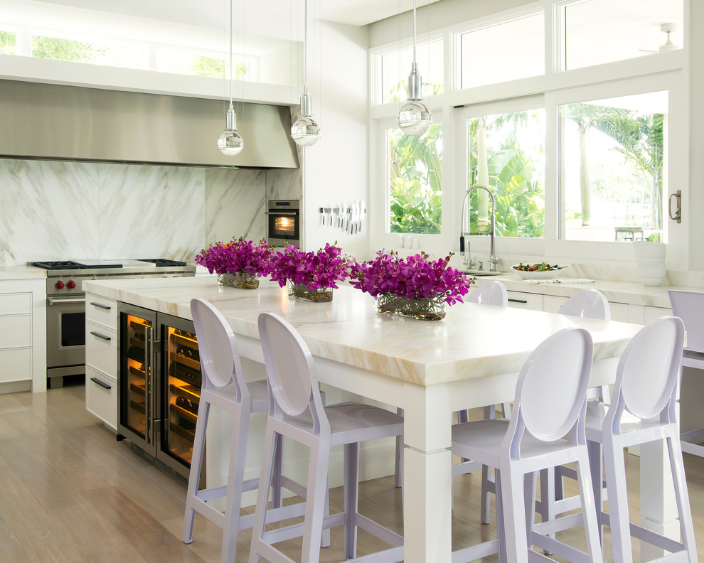 Example of a large trendy u-shaped light wood floor enclosed kitchen design in Miami with white cabinets, white backsplash, stainless steel appliances, an island, an undermount sink, recessed-panel cabinets and marble countertops