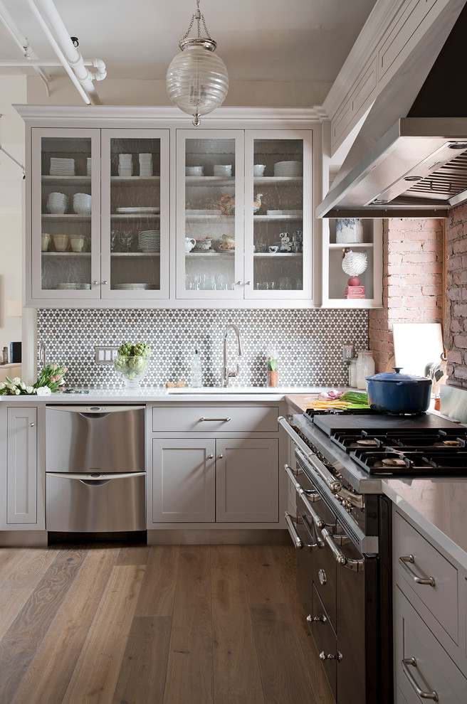 Example of a large transitional u-shaped light wood floor and multicolored floor eat-in kitchen design in New York with an undermount sink, glass-front cabinets, gray cabinets, metallic backsplash, black appliances, quartz countertops, ceramic backsplash and two islands