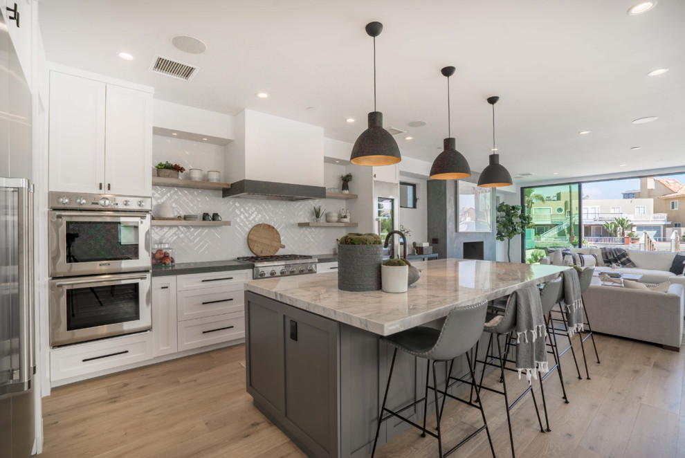 Example of a trendy l-shaped medium tone wood floor and brown floor kitchen design in Orange County with shaker cabinets, white cabinets, gray backsplash, stainless steel appliances, an island and gray countertops