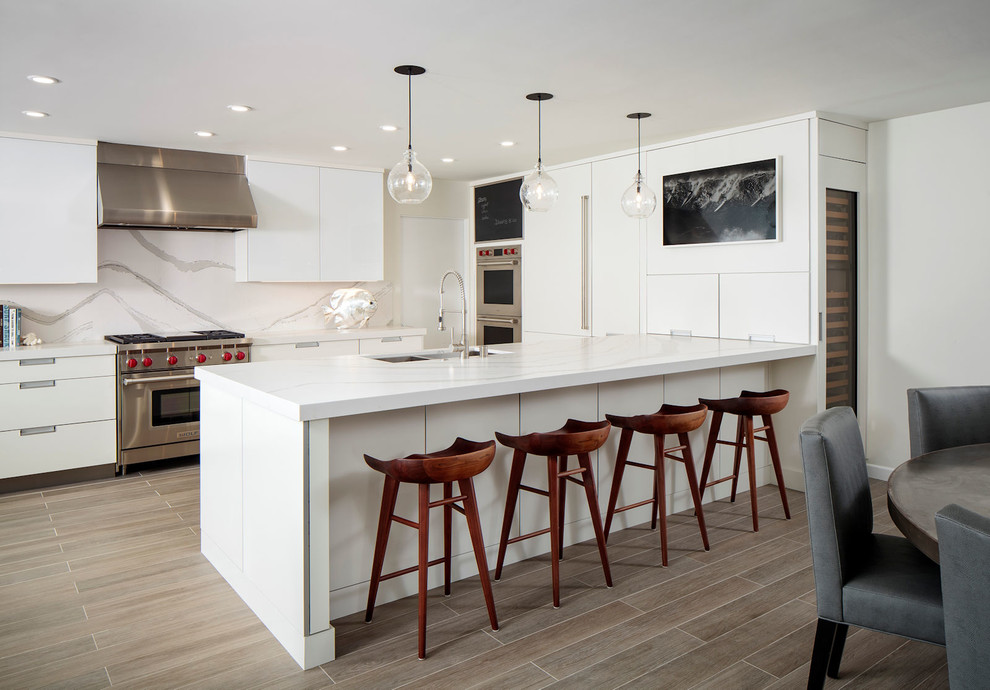 Inspiration for a contemporary u-shaped brown floor kitchen remodel in Orange County with an undermount sink, flat-panel cabinets, white cabinets, white backsplash, stainless steel appliances, a peninsula and white countertops
