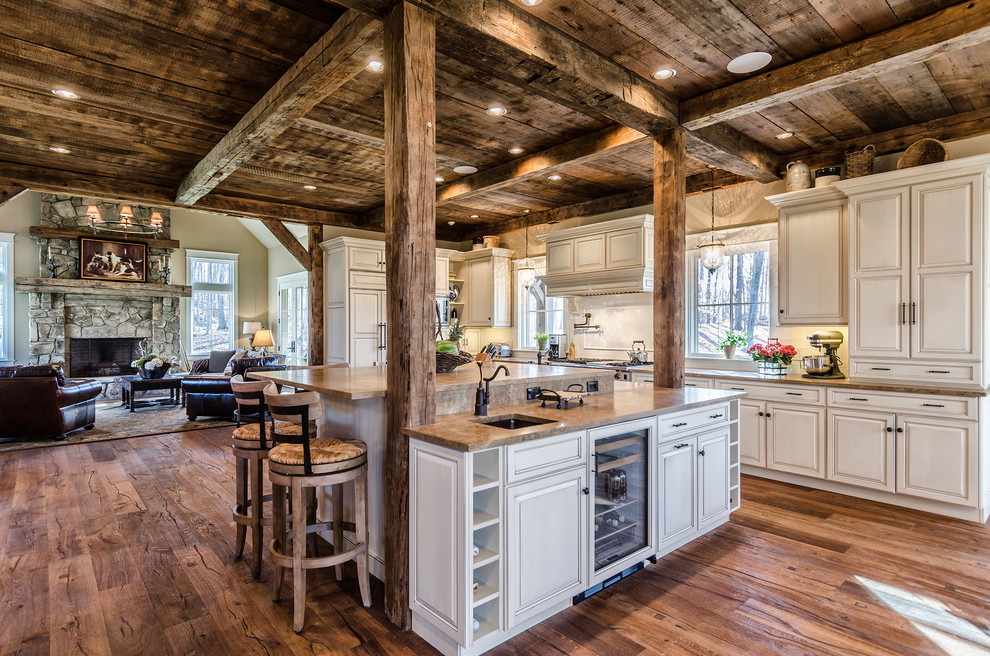 Inspiration for a rustic l-shaped open concept kitchen remodel in New York with an undermount sink, raised-panel cabinets, beige cabinets, white backsplash and paneled appliances