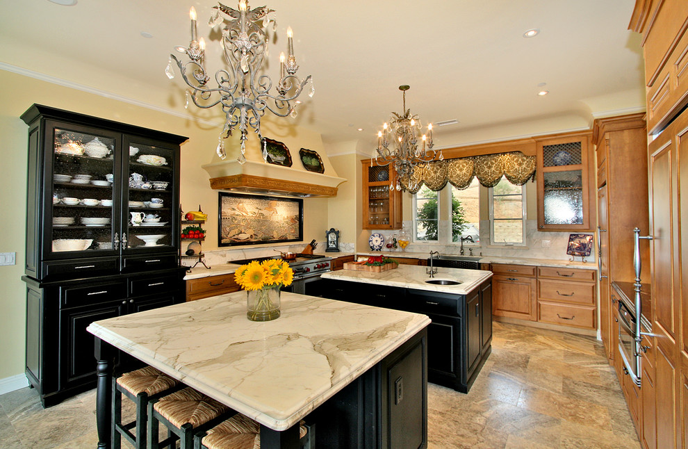 Example of a classic u-shaped kitchen design in San Diego with a farmhouse sink, marble countertops and two islands