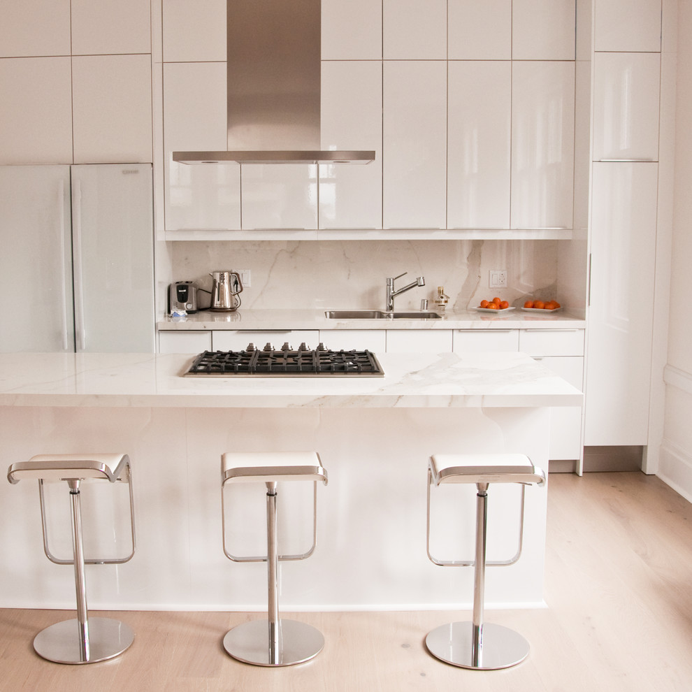 Mid-sized minimalist galley light wood floor open concept kitchen photo in San Francisco with an undermount sink, flat-panel cabinets, white cabinets, marble countertops, white backsplash, stone slab backsplash, white appliances and a peninsula
