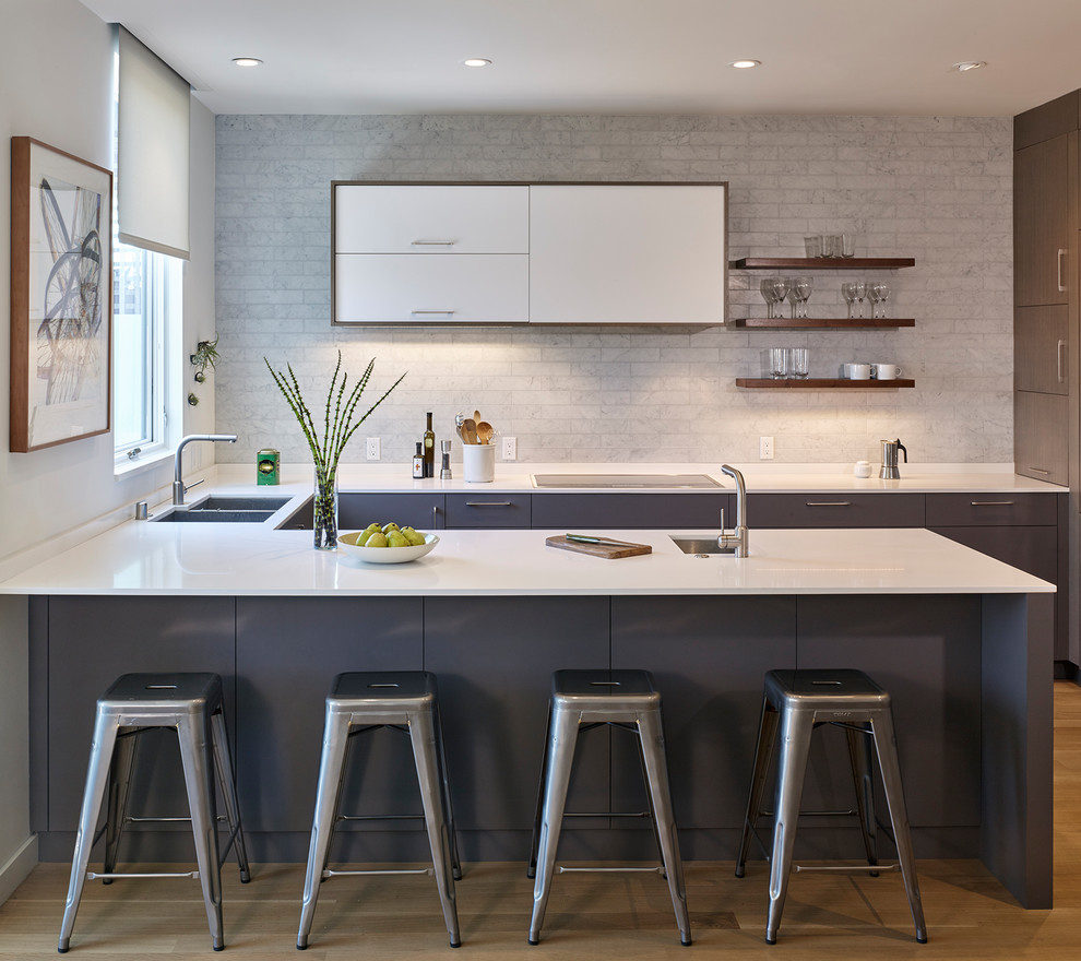 Small minimalist u-shaped medium tone wood floor and brown floor open concept kitchen photo in San Francisco with an undermount sink, flat-panel cabinets, gray cabinets, gray backsplash, a peninsula, quartz countertops, marble backsplash and white countertops