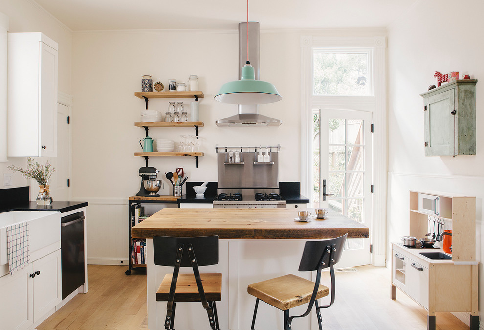 Danish light wood floor kitchen photo in San Francisco with a farmhouse sink, recessed-panel cabinets, white cabinets, wood countertops, black backsplash, stone slab backsplash, stainless steel appliances and an island