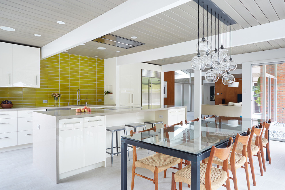 Open concept kitchen - 1950s galley open concept kitchen idea in San Francisco with white cabinets, yellow backsplash and an island