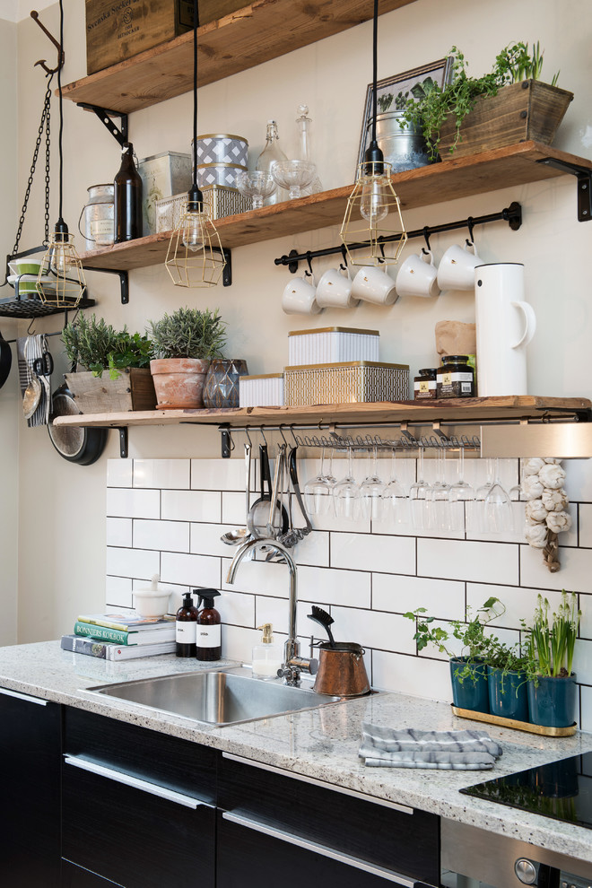 Kitchen - small rustic single-wall kitchen idea in Gothenburg with a drop-in sink, flat-panel cabinets, black cabinets, granite countertops and no island