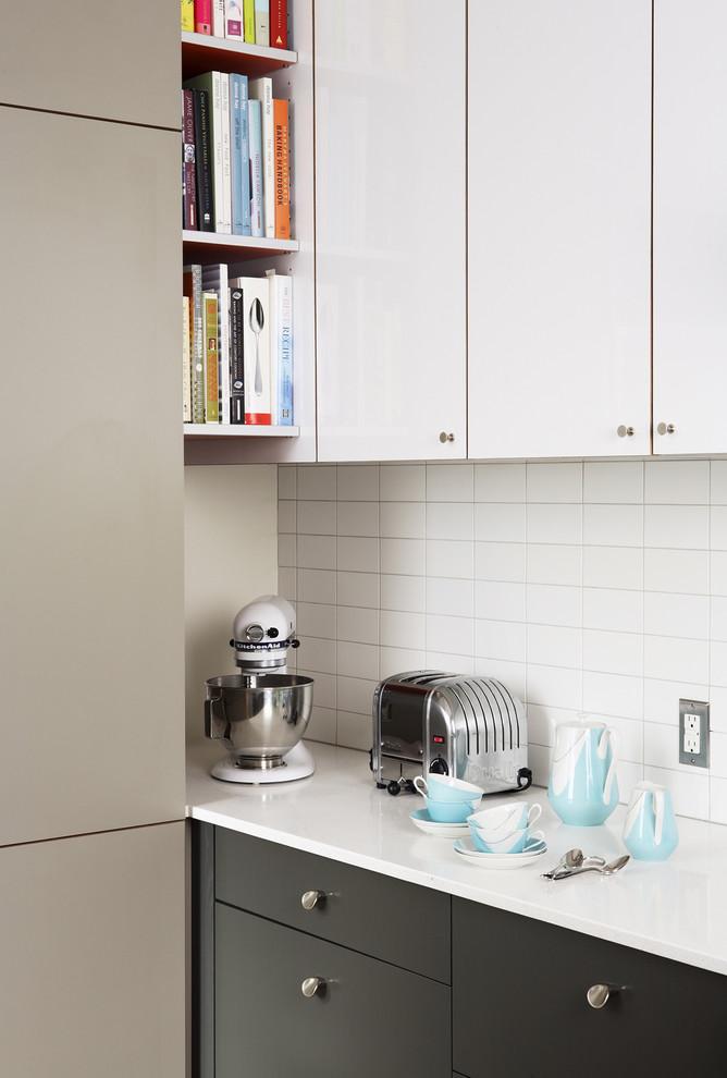 Minimalist kitchen photo in San Francisco with flat-panel cabinets and white backsplash