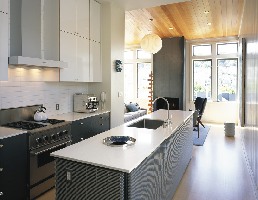 Open concept kitchen - modern open concept kitchen idea in San Francisco with stainless steel appliances, an undermount sink, flat-panel cabinets, gray cabinets and white backsplash