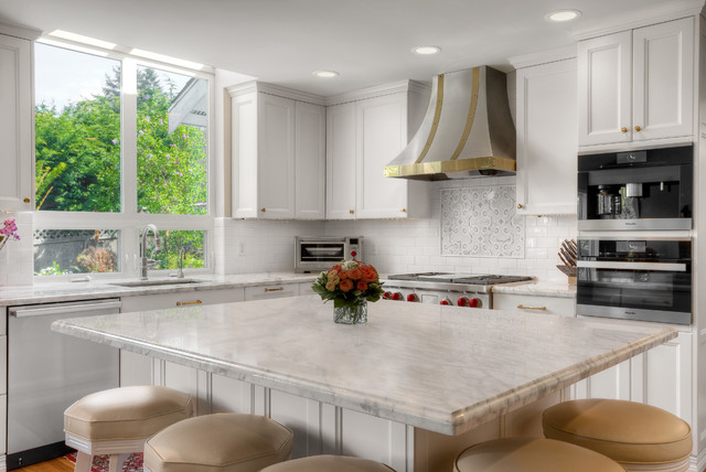 Inspiration for a mid-sized transitional l-shaped open concept kitchen remodel in Seattle with an undermount sink, flat-panel cabinets, white cabinets, marble countertops, white backsplash, subway tile backsplash, stainless steel appliances and an island