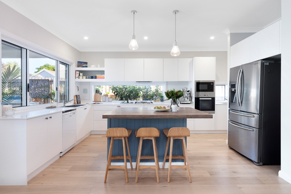 Inspiration for a contemporary u-shaped medium tone wood floor and beige floor kitchen remodel in Sydney with a double-bowl sink, flat-panel cabinets, white cabinets, wood countertops, gray backsplash, stainless steel appliances, an island and white countertops